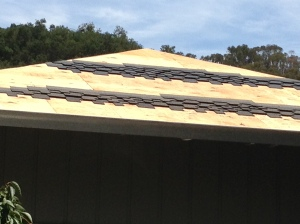 At this new roof, we don't see tar paper over the plywood yet because the construction workers are experimenting with a few different shingle patterns.