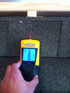 A MultiScanner® x85 scans through asphalt shingles and plywood and the tool indicates the center of a rafter at Zircon's Research & Development department. Notice the LCD screen and the SpotLite® pointing system on the shingle.