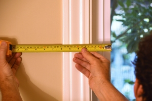 Locate the studs on an inside wall, and very carefully measure the distance from the studs to a window or door.  Tip: Don't measure off the window trim.  Measure from the edge of the glass so you know the exact same reference point can be found outside.